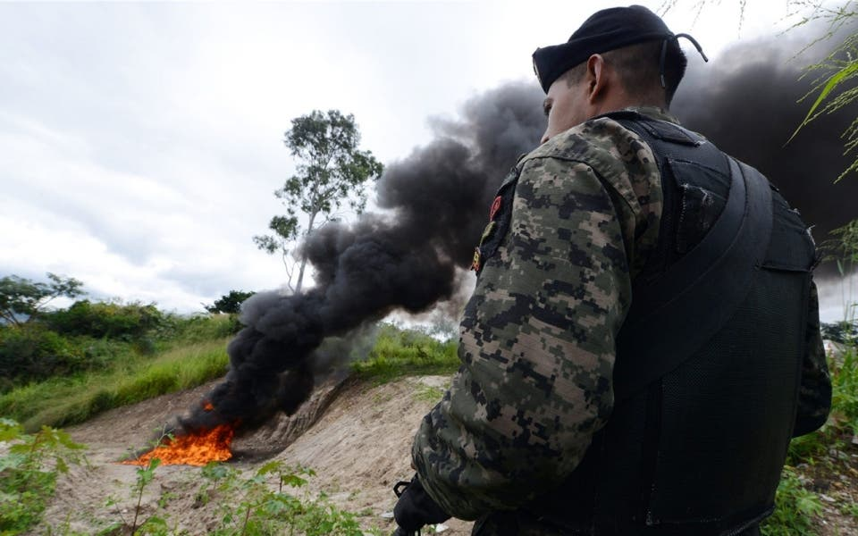 A soldier stands guard as 420 kilos of cocaine seized in La Mosquitia in Honduras are incinerated by the organized crime public prosecutor's office, in Tegucigalpa, in October 2013.Orlando Sierra / AFP / Getty Images
