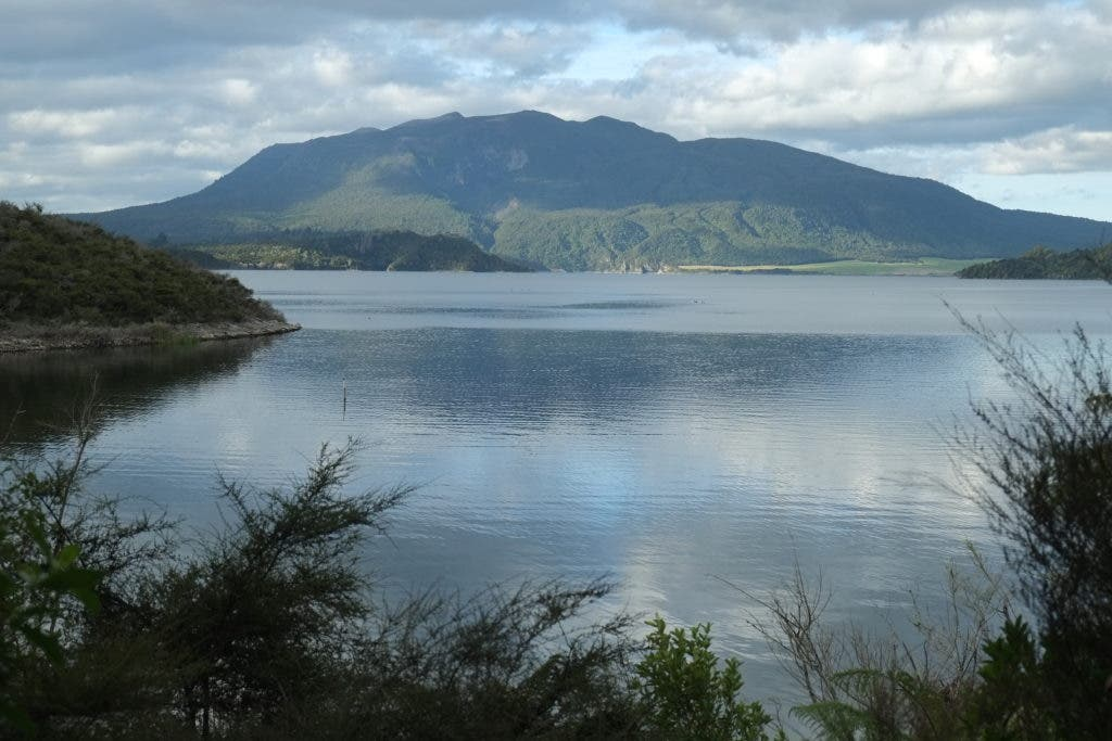 Lake Rotomahana, with Mount Tarawera in the background. Somewhere beneath the water lie the lost terraces. Credit: Wikimedia Commons.